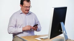 Manager in shirt holds mobile phone and smiles near computer Stock Footage