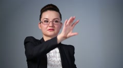 Business woman in glasses clicks on invisible touch screen Stock Footage