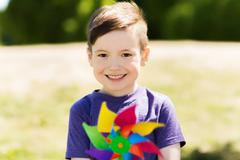 Happy little boy with colorful pinwheel at summer Stock Photos