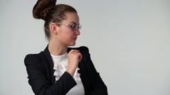Woman in black suit and glasses poses in grey studio Stock Footage