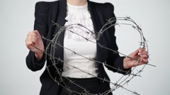 Girl in black jacket holding heart of barbed wire fence Stock Footage