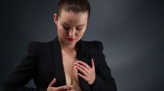 Pretty woman touches her breasts in black jacket in black studio Stock Footage