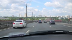 Many cars ride on wide asphalt road of city at summer day Stock Footage