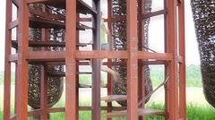 Woman climbs spiral staircase inside wicker construction outdoor Stock Footage