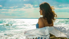 Young female on seashore, wind waving scarf in her hands. Woman enjoying freedom Stock Footage