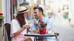 Couple talking at outdoors cafe sitting by table on street Stock Footage