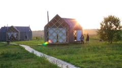 Sun and people near small houses in village at summer day Stock Footage