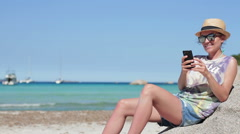 Brunette girl reading or writing sms on sea background at the beach HD Stock Footage