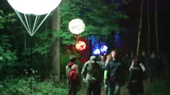 People walk in forest with ball lanterns at night. Focus on trees Stock Footage