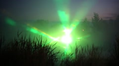 Beautiful laser show on lake with stage outside at night Stock Footage