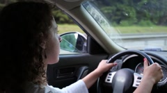 Hands and head of woman driving car on highway at summer day Stock Footage