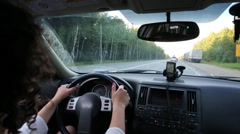 Back of woman driving car on highway among forest at summer day - stock footage