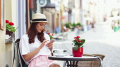 Young happy woman browsing internet on smartphone at outdoors cafe Stock Footage