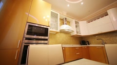 Empty kitchen with gilded shiny furniture and built-in appliances - stock footage