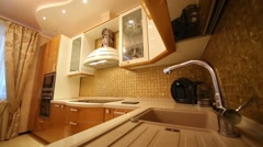 Sink in kitchen with gilded furniture and built-in appliances - stock footage