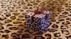 Nice small box with gift on double bed with leopard print Stock Footage