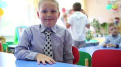 Two boys sit at table in kindergarten and look at each other. Stock Footage