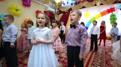 Twenty one little boys and girls perform in hall and woman stands Stock Footage