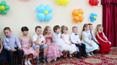Twelve little boys and girls sit in hall decorated with balloons Stock Footage