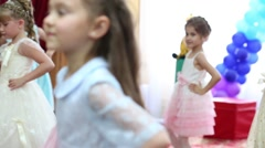 Thirteen little girls dance in hall decorated with balloons Stock Footage
