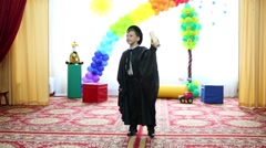 Boy in wizard hat and cloak performs at festival in kindergarten Stock Footage