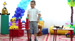 Boy among toys performs at festival in kindergarten Stock Footage
