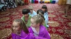 Six girls dance in kindergarten and five children look at their Stock Footage