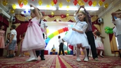 Twenty four children dance in pairs in kindergarten and two women Stock Footage
