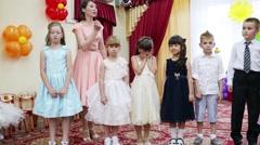 Fourteen children and two women perform in kindergarten Stock Footage