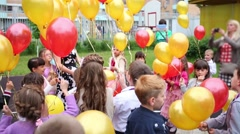 One woman and fourteen happy children launch balloons into sky Stock Footage