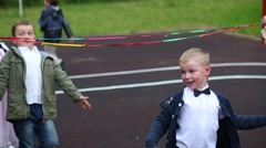 Ten children pass under the rope on playground in kindergarten Stock Footage