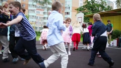 Facilitator and throwing paper children on playground Stock Footage