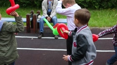 Four boys fight with swords balloons at playground Stock Footage