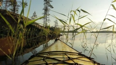 Kayak moving between reeds by a rocky shore at a lake in Finland Stock Footage