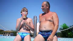 Senior and young boy with tropical cocktail near swimming pool Stock Footage
