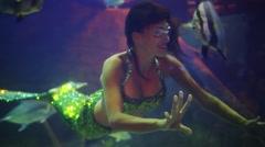 Mermaid touches fish at Oceanarium Sochi Discovery World Aquarium Stock Footage