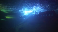 Mermaid and fishes swim in pure water with lights near sunken ship Stock Footage