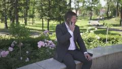 Businessman sitting on wall in park answers smartphone. Stock Footage