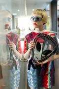 Fashion photo. Girl in a stylish bright clothes in a boutique with UFO bag. - stock photo