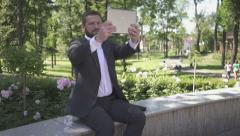 Businessman takes selfie by tablet, sitting on wall in park. Stock Footage