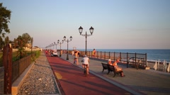Resting people walk at sea quay with lanterns at summer evening Stock Footage