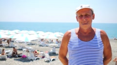 Portrait of elderly man in striped jersey and white cap on beach Stock Footage