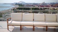 Seating area with beige sofa on rooftop overlooking city Stock Footage