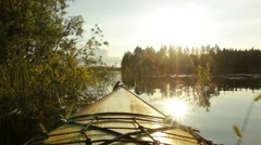Kayak moving towards bright sun at a lake Stock Footage