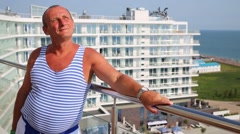 Portrait of elderly man in striped vest on terrace Stock Footage