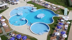 Large swimming pool with tourists on site Hotel Stock Footage