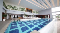 Hall with empty pool and sun loungers in modern hotel Stock Footage