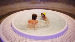 Happy boy and girl play and spin in round jacuzzi in hotel Stock Footage