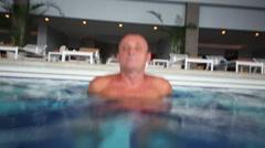 Elderly man with open eyes smiles underwater in pool Stock Footage