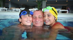 Grandfather and two children smiles in swimming goggles underwater Stock Footage
